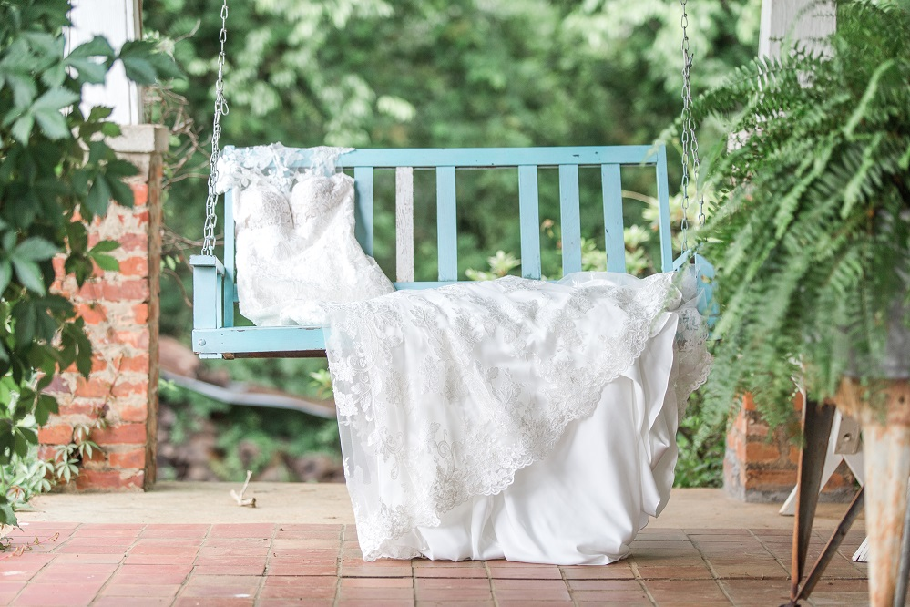 bridal gown laying on farmhouse porch swing